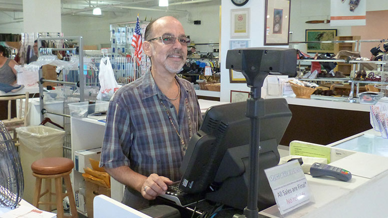 Man volunteering at cash register in Revivals store.