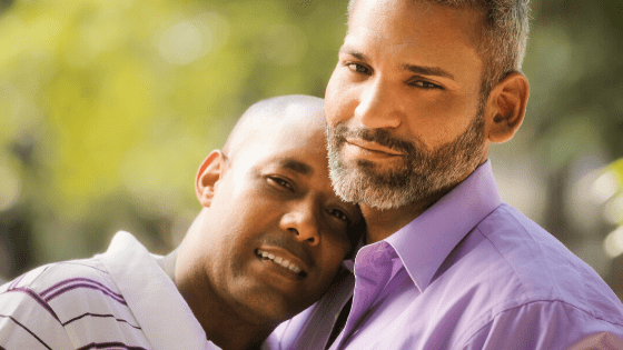 Two men embraced looking at the camera in a park