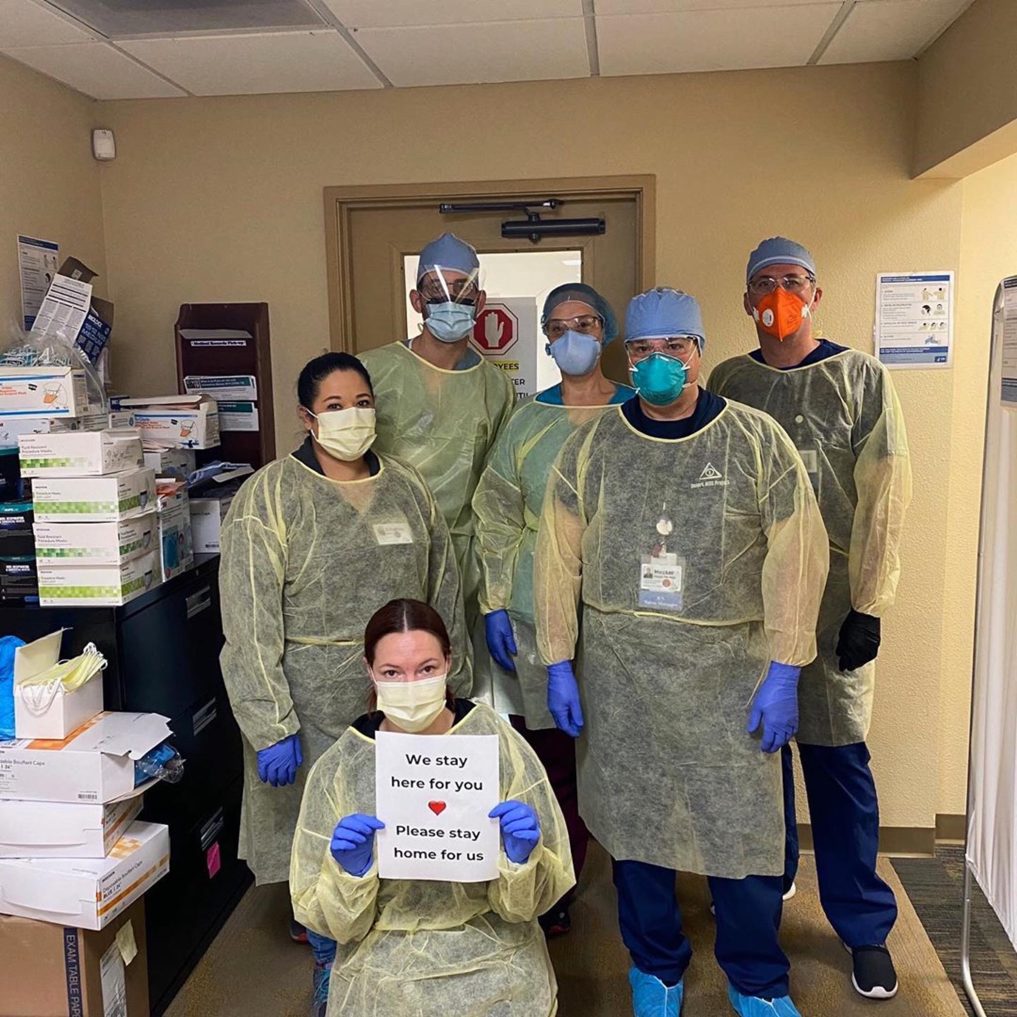 DAP Medical Team Wearing Masks and holding a sign that says we stay here for you, you stay home for us.