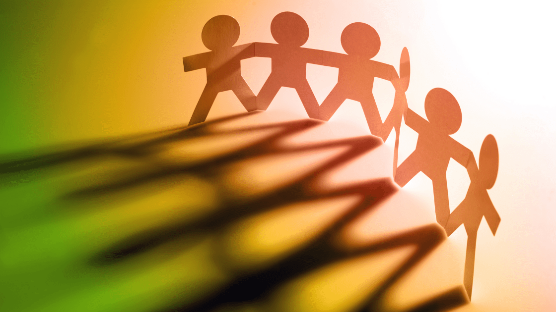 Six people holding hands, casting shadows